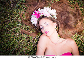 sleeping beauty: filtered image of beautiful brunette young woman in lotus flower crown and pink makeup lying gracefully on green grass outdoors copy space background