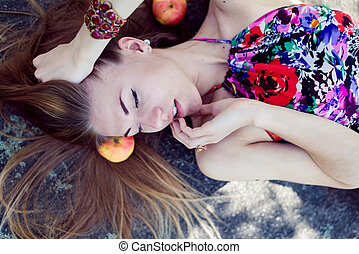 sleeping beauty: portrait of beautiful blond young woman having fun sensually smiling & looking at copy space on summer outdoors background closeup