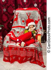 Sleeping boy in chair holding reindeer toy plush