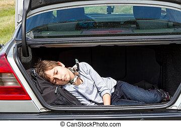 Sleeping boy in the trunk of a car