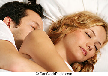 sleeping couple - a attractive young couple is sleeping in...