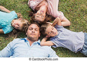 Sleeping family lying on the grass in a circle