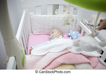 Sleeping four month baby boy lying in cot with mobile