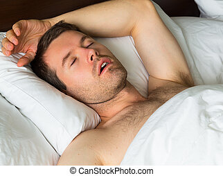 Sleeping man - A sleeping man in bed with his arm up