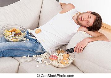 Sleeping man and junk food