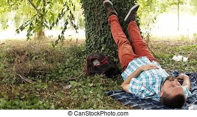 Sleeping Man Leaning Feet Against Tree