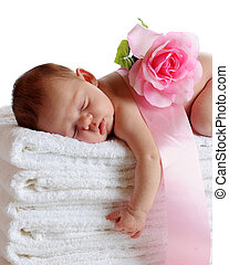A beautiful newborn sleeping soundly on a stack of white towels, a ribbon and pink rose on her back.