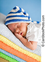 Sleeping newborn baby closeup portrait on colorful towels...