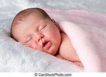 Sleeping newborn baby girl on tummy