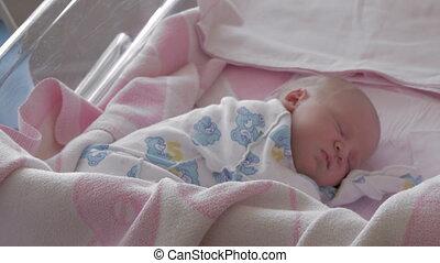 Sleeping newborn baby in maternity hospital