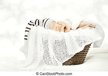 Sleeping newborn baby in woolen hat lying in basket with blanket over white soft background.