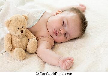 sleeping newborn baby with teddy bear