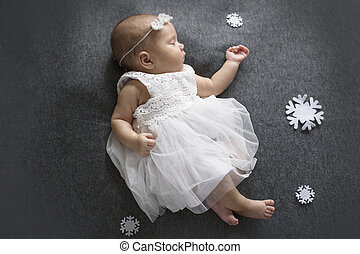 Sleeping newborn girl in a white dress on a dark gray background