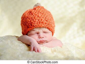 sleeping newborn wearing pumpkin hat