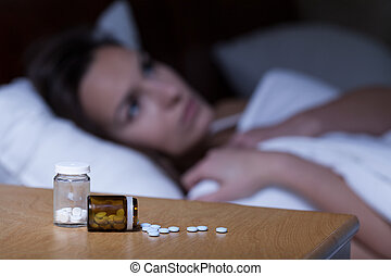 Sleeping pills lying on night table and woman trying to...