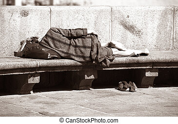 Sleeping the tramp - A homeless woman sleeping on a park...