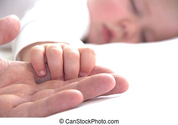 Sleeping toddler boy is holding father's hand