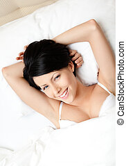 Sleeping woman in the bed with white bed linen, white ...