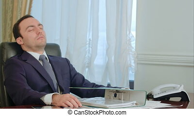Sleeping young businessman awakened by phone call in office