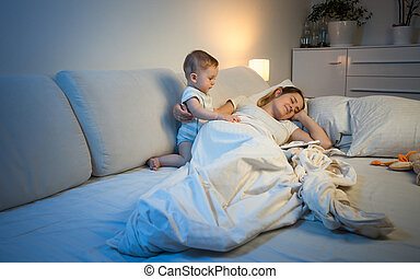 Sleepless baby boy waking up his mother sleeping in bed -...
