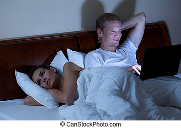 Sleepless wife and husband with laptop
