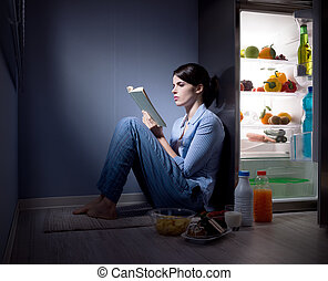 Sleepless woman reading in the kitchen