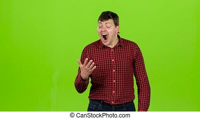 Sleeps a man, yawns, he is sleepy and wants to go to bed. Green screen