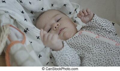 Sleepy baby in bassinet - Sleepy baby lying in bassinet on...