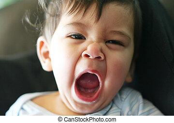 Sleepy baby yawning