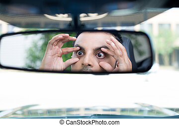 Closeup portrait, funny young man driver looking at rear view mirror trying to stay awake using hands to open eyes, isolated interior car windshield background