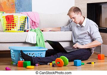 Sleepy father trying to work among laundry