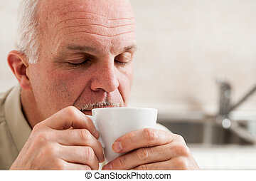 Sleepy man holding little coffee cup to his mouth