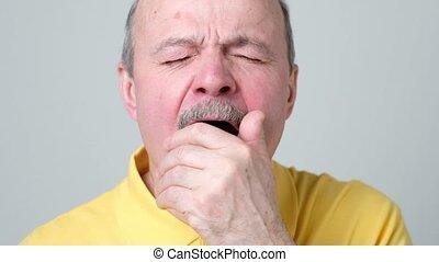 sleepy man in yellow shirt yawning, morning and wake up,...