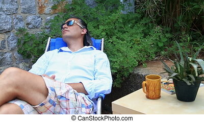 Sleepy man relaxing in the garden