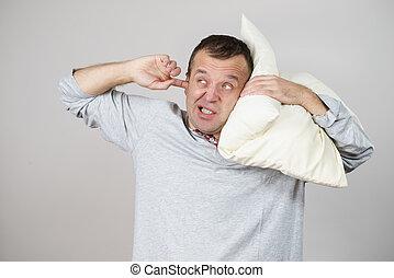 Sleepy man with pillow closing his ear
