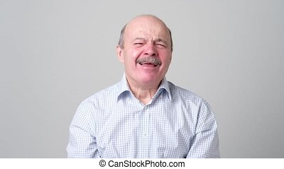 Sleepy mature bald man with mustache is yawning, because he ...