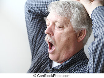 sleepy older man yawns - tired senior man stretches and...