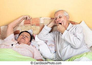 Sleepy senior couple in bed