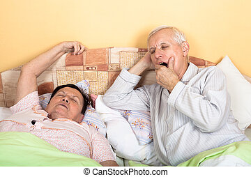 Sleepy senior couple in bed