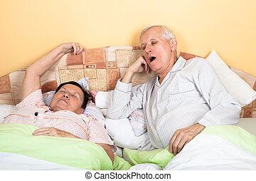 Sleepy senior couple yawning in bed