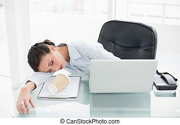 Sleepy stylish brunette businesswoman lying on her desk in ...
