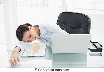 Sleepy stylish brunette businesswoman lying on her desk in...