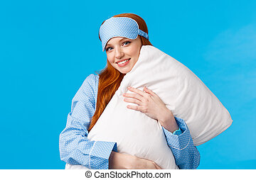 Sleepy time. Lovely and feminine glamour redhead girl with sleep mask, wearing nightwear, hugging pillow and smiling, wishing sweet dreams, standing blue background upbeat