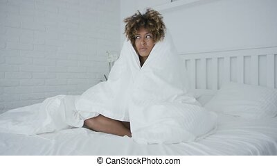 Sleepy woman cuddling in blanket - Young curly ethnic model...
