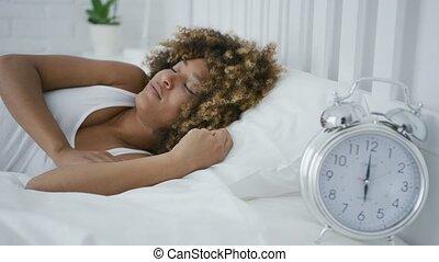 Sleepy woman looking at alarm - Young ethnic model lying on...