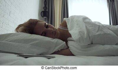 Sleepy woman turns alarm off while awakening in the morning....