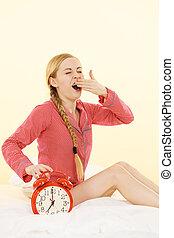 Sleepy woman wearing pajamas holding clock