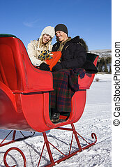Sleigh ride. - Young Caucasian couple in sleigh holding a...
