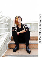Slender Asian American Woman Sitting On Steps