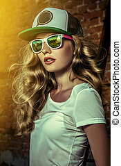 slender - Beautiful modern girl near the brickwall. Youth...